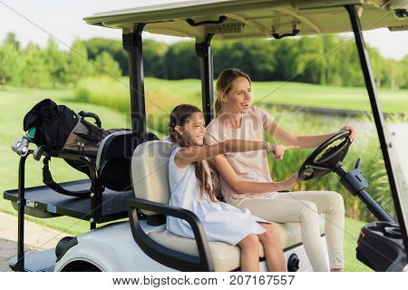 Girl And Woman On A White Golf Cart. Girl Showing A Hand Forward