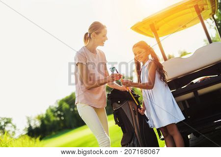 A Woman Gives The Girl A Golf Club, Which She Just Pulled From A Bag For Clubs