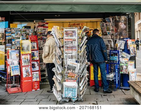 PARIS FRANCE - OCT 3 2017: People Seniors buying international newspapers at kiosk with socking title photos at about the 2017 Las Vegas Strip shooting in United States with about 60 fatalities and 527 injuries