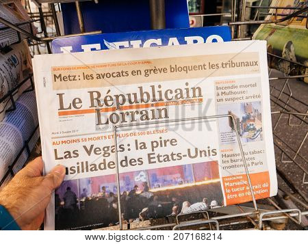PARIS FRANCE - OCT 3 2017: Man buying Le Republican Lorrain newspaper with socking title and photo at press kiosk about the 2017 Las Vegas Strip shooting in United States with about 60 fatalities and 527 injuries