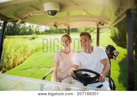 Happy Couple Rides On A White Golf Cart Playing Golf. The Woman Laid Her Hand On The Man's Shoulder