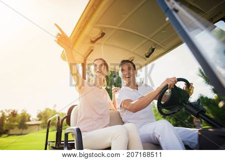 Happy Couple On A Golf Cart Rides To Play Golf