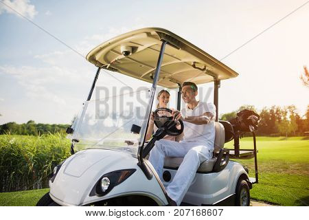 Happy Man And Woman Are Sitting In A White Golf Cart, Which Stands On The Road Of A Golf Club