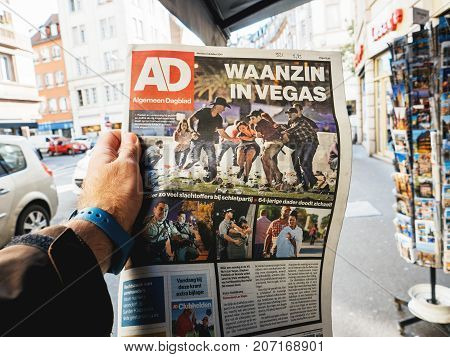 PARIS FRANCE - OCT 3 2017: Man buyingDutch algemeen dagblad newspaper with socking title and photo at press kiosk about the 2017 Las Vegas Strip shooting in United States with about 60 fatalities and 527 injuries