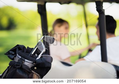 Close Up Photo. Golf Clubs In The Foreground, Man With A Woman In A Golf Cart On A Background