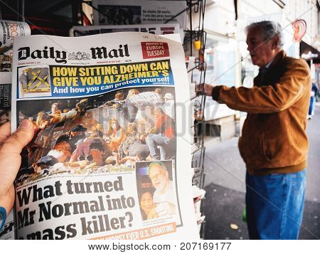 PARIS FRANCE - OCT 3 2017: Man buying Daily Dail newspaper with socking title and photo at press kiosk about the 2017 Las Vegas Strip shooting in United States with about 60 fatalities and 527 injuries