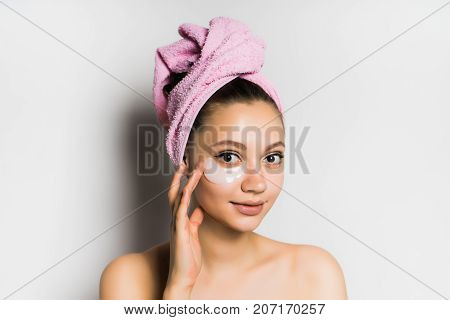 a girl with a towel tied around her head smiling puts a mask on her face