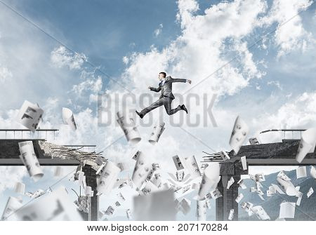 Businessman jumping over gap in bridge among flying papers as symbol of overcoming challenges. Skyscape and nature view on background.