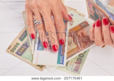 Manicured hands holding paper money of Myanmar. Senior woman hands with luxury red manicure. Well-groomed hands and Burma money.