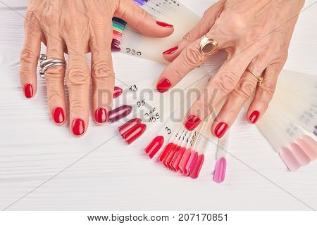 Senior woman hands with red manicure. Old woman well-groomed hands wearing rings. Female manicured hands and nails color samples.