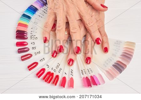 Senior woman hands with red nails. Old woman hands with perfect red manicure, nail samples collection. Feminine beauty and aristocratism.
