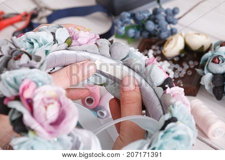 Handmade headbands making, home workshop. Unrecognizable woman artisan decorating hair hoop with flowers and ribbons, close up. Art, handicraft, creative concept