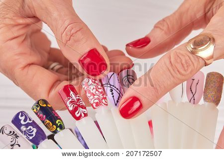 Female hands choosing nail design. Old woman hands with red manicure holding collection of nails art samples close up. Templates for beauty salon.