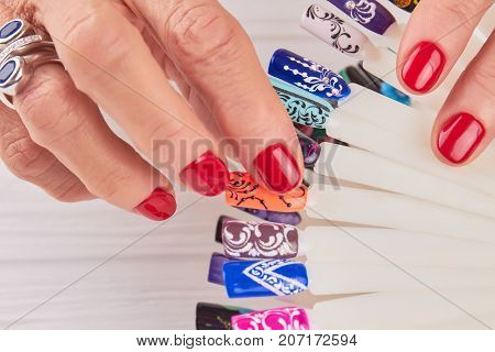 Manicured hands, nail art samples close up. Beautiful female hands holding samples of nail art design close up. Nail art on plastic tips.