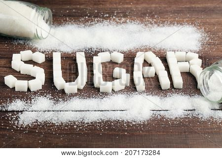 Inscription Sugar by sugar cubes on brown wooden table