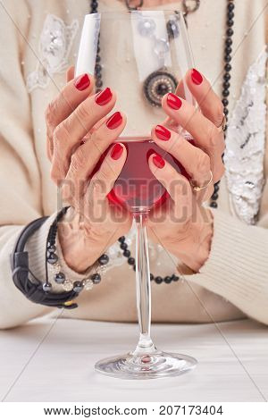 Glass of red wine in female hands. Well-groomed old woman hands holding large glass with wine. Beautiful red manicure.