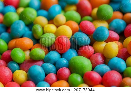Sugar candy sweet background. Confections in green yellow red color drops. Bright texture and round forms of raisins or nuts.