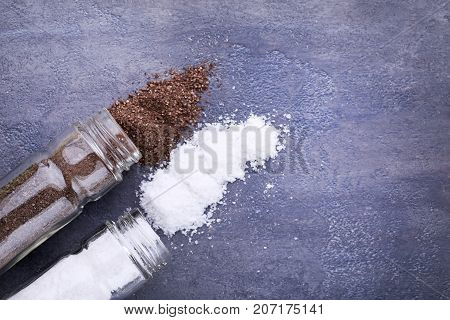 Salt And Pepper In Shakers On Grey Wooden Table