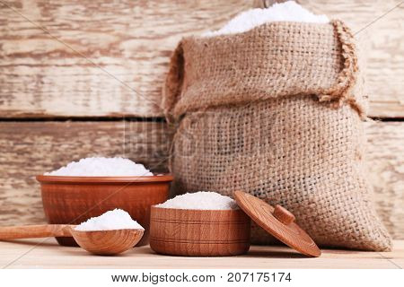 White Sea Salt In Scoop, Sackcloth And Bowls On Brown Wooden Table
