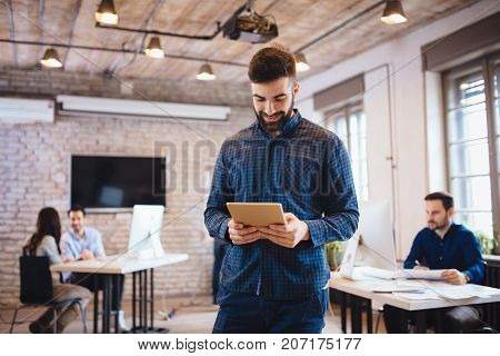 Portrait of handsome male company trainee in modern office