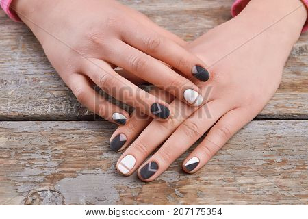 Female hands with trendy design manicure. Woman well-groomed hands with stylish manicure on old wooden background. Trending nail art design.