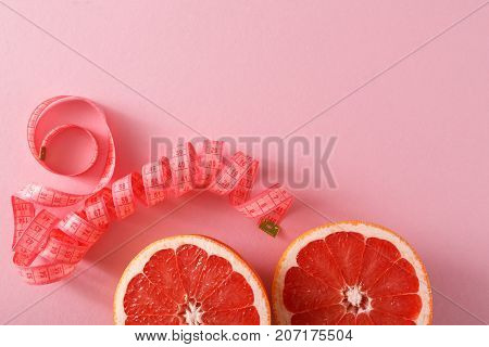 Dieting background, grapefruit slice with measuring tape on pink backdrop copy space. Diet, healthy eating, slimming concept