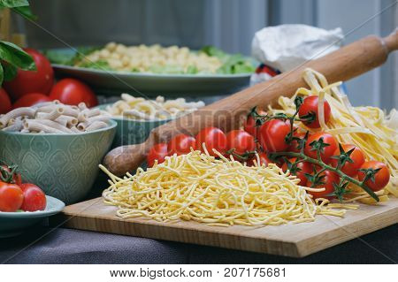 Close-up of unprepared italian pasta with fresh tomatoes