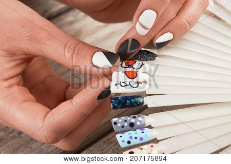 Close up of female hands and nail art samples. Woman hands with stylish manicure holding nails art palette. Nail art concept.