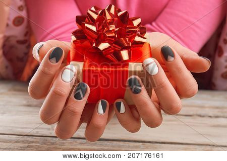 Handmade gift box in female hands. Woman manicured hands holding box with gift close up. Concept of holidays and celebrations.