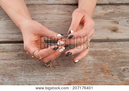 Manicured hands with golden rings. Woman hand with beautiful manicure putting on golden ring on finger.