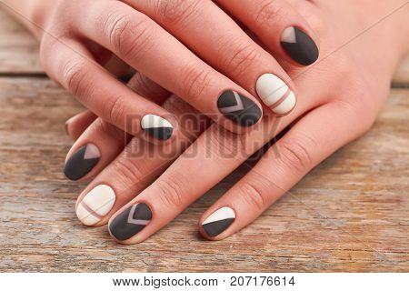 Female hands with stylish manicure. Woman hands with black and white matte manicure on old wooden background close up. Salon beauty and spa.