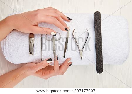 Manicured hands and equipment for manicure. Young woman hands with beautiful manicure on white towel with instruments for manicure. nails salon and spa.