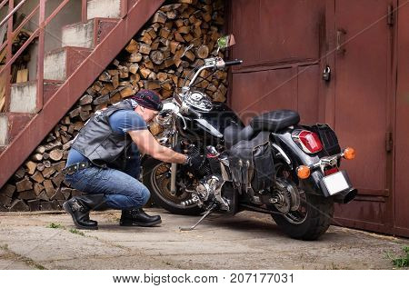 The biker inspects his motorcycle in the courtyard of his house.