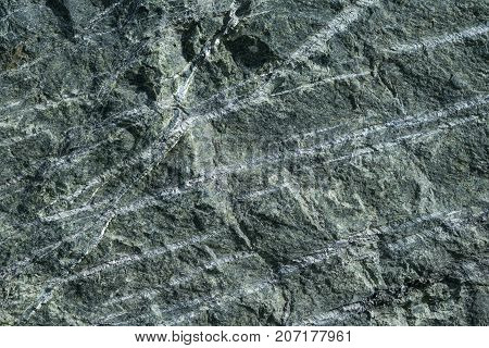 Surface grey granite stone with light lines and streaks. On granite there are bumps and pits. The structure of granite stone in cross section.