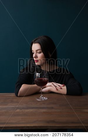 Lonely young female in bar. Melancholic mood. Sad woman with red wine on blue background with free space, unsuccessful romantic date. Problems in life, sadness concept