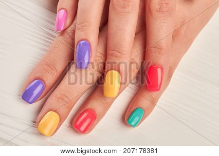 Female fingers with colorful nails. Beautiful woman hands with pastel colors nails on white wooden background. Well-groomed hands with summer manicure.