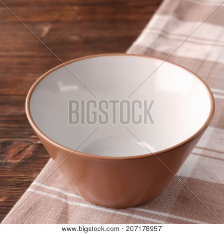 Bowl Of Soup Is Empty On The Tablecloth. Brown On A Wooden Table. Warm Shade.