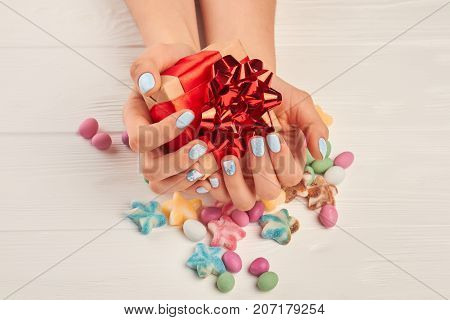 Box with gift in manicured hands. Young woman hands with winter manicure holding little gift box, multicolored candies on white wooden background. Christmas celebrations concept.