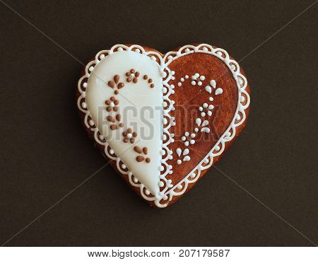 Gingerbread cookie in the shape of heart with tradional decoration. Black paper background.