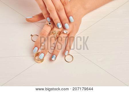 Manicured hands wearing golden rings. Young woman hands with gentle manicure and many golden rings with stones. Well-groomed hands of young woman and jewelry.