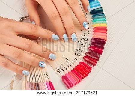 Manicured hands and collection of nail samples. Young woman nails covered with gentle blue polish, nail colors palette.