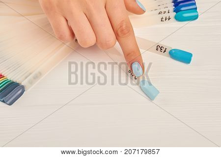 Index finger choosing color on nail palette. Female manicured finger indicating on nail color sample. Woman finger with light blue varnish on nail. Nail salon and spa.