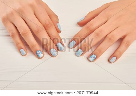 Winter design manicure on female hands. Well-groomed woman hands with gentle manicure. Young woman manicured hands on white wooden background.