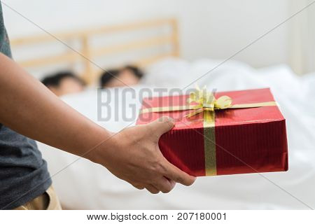 Closeup red gift box surprise but Wife woman or girlfriend having an affair with a married man sleeping on the bed under pillow at home