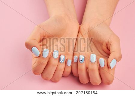 Gentle hands with blue winter manicure. Well-groomed female hands with beautiful nail design. Manicured hands on pink background.