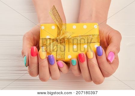 Little gift box in female manicured hands. Woman hands with pastel nail polish holding yellow dotted box with gift.