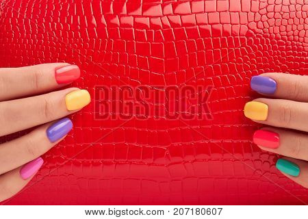 Close up red bag in manicured hands. Detail of red lacquered handbag in woman hands with multicolored manicure. Female fashion accessory.