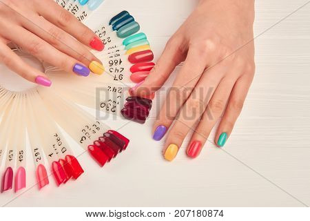 Well-groomed hands and nail color samples. Female hands with pastel manicure and nail color palette. Manicure nail polish color samples.