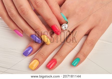 Manicured fingers touching diamond on ring. Engagement ring on female manicured hand. Wedding ring on woman finger.