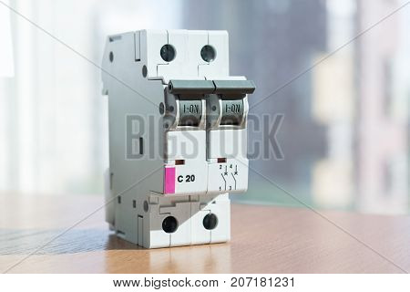 Two-pole modular circuit breaker is on the table front view. Electrical switch to protect home wiring and appliances. On the front there is a status indicator on off.